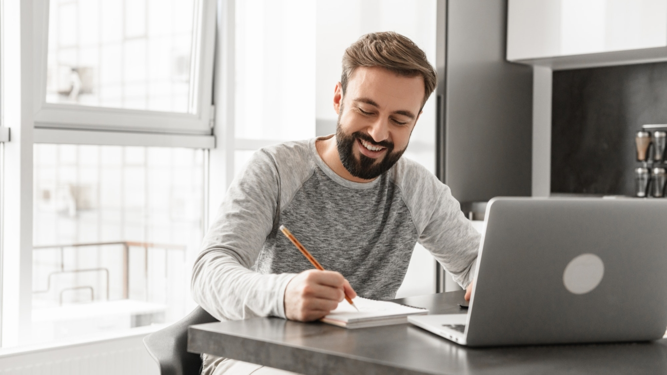 Portrait of a smiling young man working on laptop computer